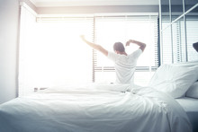 Man Wake Up And Stretching On Bed In Morning With Sunlight