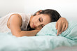 Young tired woman sleeping in bed.