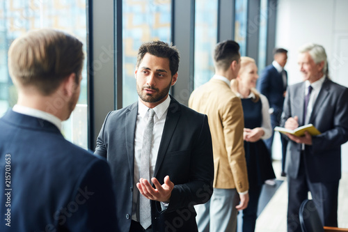 Photo Confident handsome mixed race businessman with beard sharing his opinion with fo