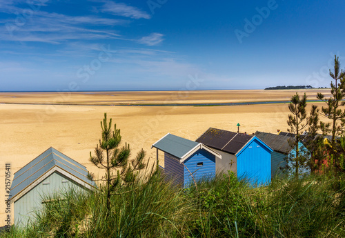 Fotomural seaside beach huts at low tide against beautiful beach and blue sky, Wells Next