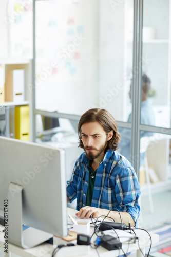 Concentrated busy young IT specialist with beard and mustache focusing on comput Fototapeta