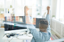 Ecstatic Young African-American Software Developer Raising Hands In Excitement While Achieving Success In Web Development, He Sitting In Front Of Computer Behind Glassy Wall