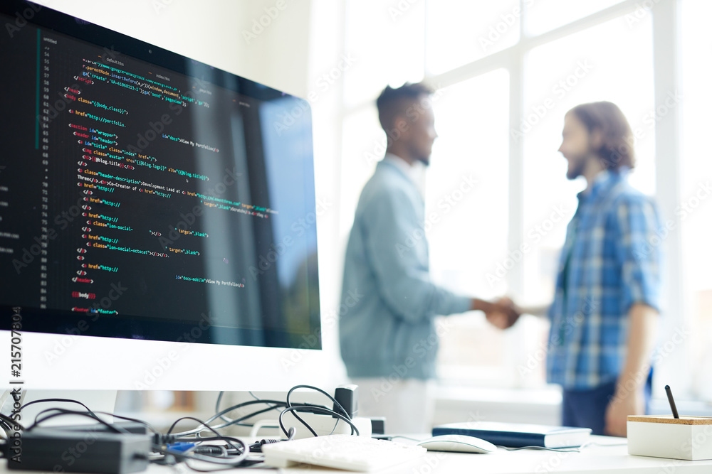 Fototapeta Hipster programmer and African entrepreneur making handshake in background, focus on computer monitor with programming code and messy cables on table