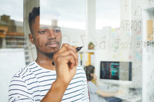 Serious Concentrated Handsome Young African-American Web Developer Using Programming Language For Coding And Writing It On Glassy Wall In Office