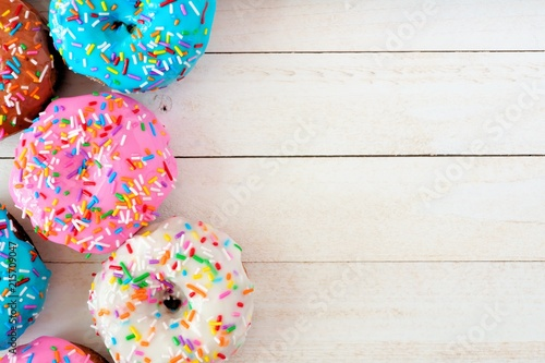 Side border of assorted donuts with pastel colored icing and sprinkles against a white wood background