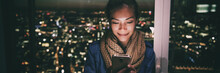 Woman Texting Instant Messaging Text On Mobile Phone Online At Night - Bright Light From Screen Illuminating Young Asian Girl In London City Background Banner Panorama.