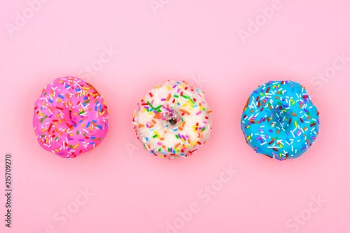 Three assorted donuts with pastel colored icing and sprinkles against a soft pink background. Minimal concept.