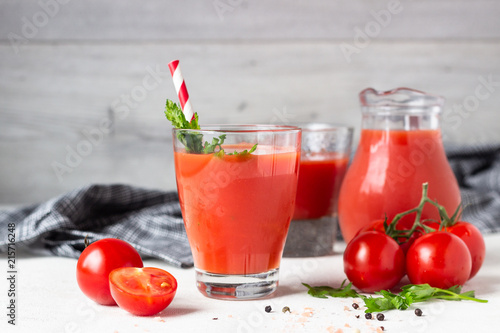 Fotobehang Sap Tomato juice with fresh tomatoes, parsley, sea salt and pepper on light grey background. Vegetable drink.