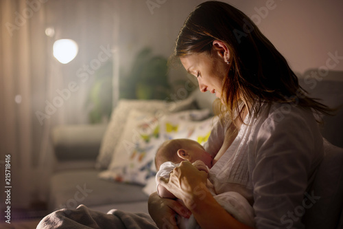 Cuadros en Lienzo Young beautiful mother, breastfeeding her newborn baby boy at night