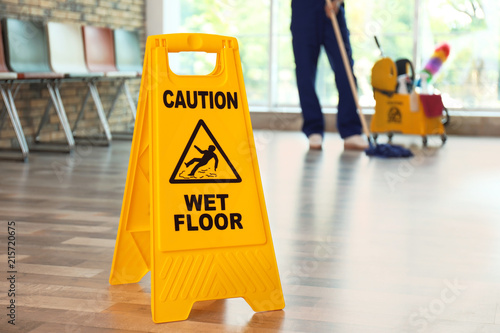 Fotografia  Safety sign with phrase Caution wet floor and blurred cleaner on background