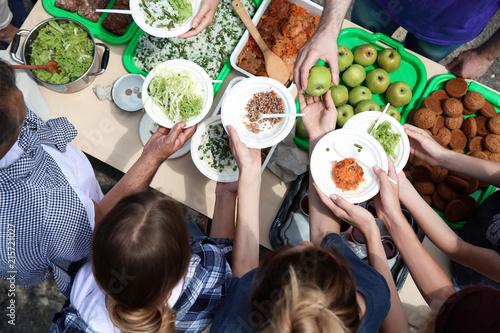 Fototapeta Volunteers serving food for poor people outdoors, top view