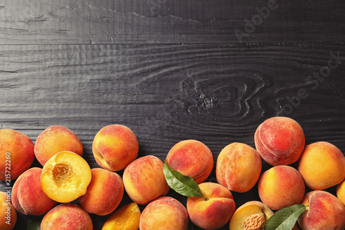 Flat lay composition with ripe peaches on wooden background