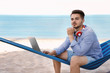 Young man with laptop and headphones sitting in hammock at seaside