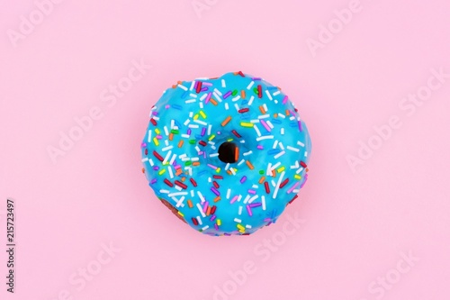 Single donut with pastel blue icing and sprinkles against a soft pink background. Minimal concept.