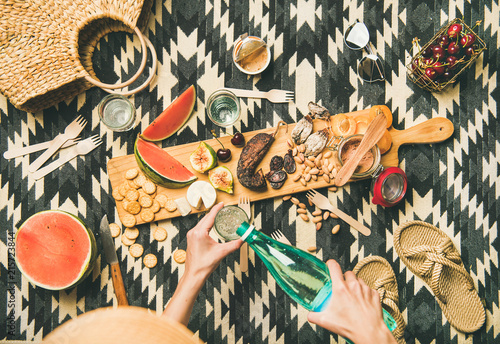 Keuken foto achterwand Summer picnic setting. Flat-lay of fresh fruit, sausage, nuts, pate, cracker, cheese, straw accessories and woman hands pouring mineral water over linen blanket, top view. Outdoor gathering or lunch