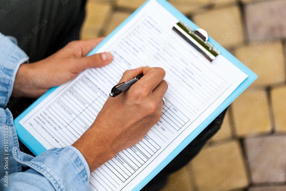 Fototapeta Closeup of a Person Filling a Track Record