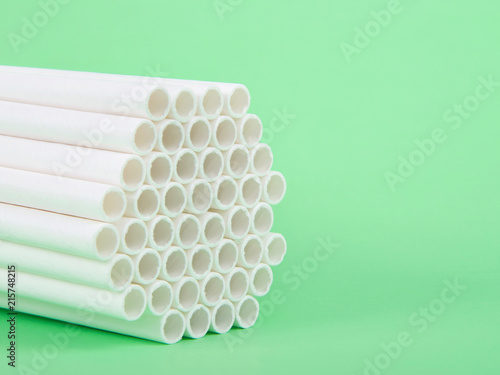 Dozens of biodegradable eco-friendly paper straws bundled together facing forward on a green background with copy space. Many cities are now banning single use plastic straws.