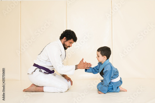 Father and little kid son are engaged in wrestling jiu-jitsu in the gym in a kimono. Trainer teaches child the methods and positions of single combat, karate or aikido. Sport and healthy in family