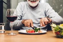 Happy Senior Man Eating Pork Steak On Table At Restaurant