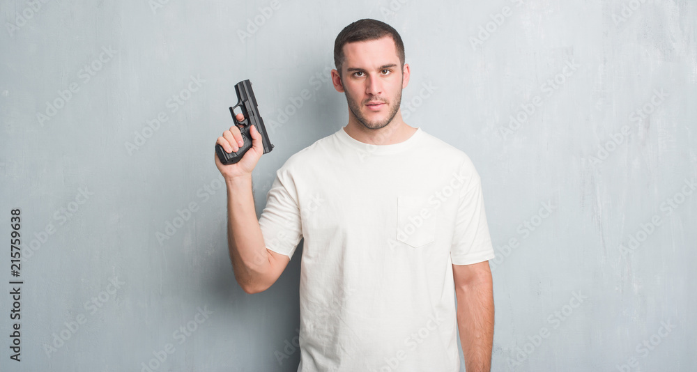 Fototapeta Young caucasian criminal man over grey grunge wall holding gun with a confident expression on smart face thinking serious