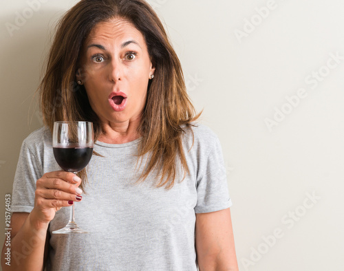 Middle age woman drinking red wine in a glass scared in