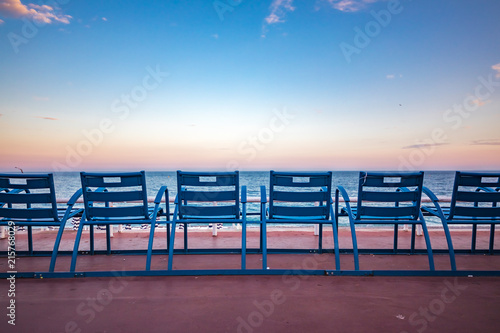 Mediterranean Sea and famous blue chais on Promenade des Anglais at sunset in Ni Canvas Print
