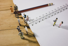 Miniature Business People Meeting On Wooden Table With Pencil And Notebook In Vintage Tone.