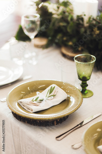 Green decorated cutlery with plant leaves and white napkins on wedding table. Rustic style
