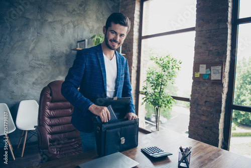 Fototapeta Attractive handsome young brunet bearded executive worker smiling cheerful man, accountant at workstation workplace. Finishing, collecting things in breif-case after work day goes home obraz