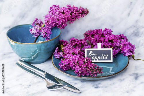 Foto op Canvas Lilac Spring Table Setting with Vintage Blue Cutlery and Lilac Flowers and Bon Appetit Text on a Wooden Background.Floral Table Decor