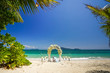 A wedding arch in traditional Thai style from white flowers on the shore of an exotic beach under palm branches.