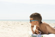 Portrait of relaxing boy in hat and glasses on beach