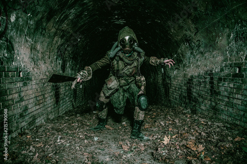 Photo  Post apocalyptic mutant creature or survivor in tatters and gas mask jumps out o