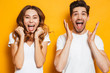 canvas print picture - Photo of beautiful admired couple man and woman in basic clothing screaming in surprise or delight and touching cheeks, isolated over yellow background