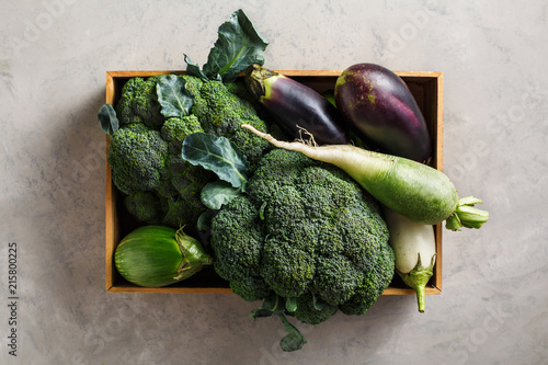 Green vegetables in a wooden box, top view.