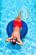 Man On Tube In Swimming Pool, Man With Sunglasses And Red Swimming Trunks On Inner Tube