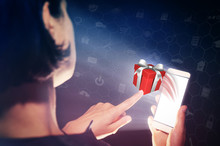 Image Of A Woman With A Smartphone In Her Hand. She Presses On The Gift. Concept Of Gift Giving, Choice Of Gifts.