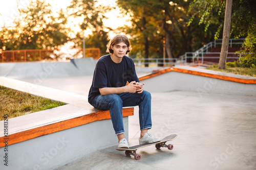 Young skater in black T-shirt and jeans dreamily looking in camera spending time at modern skate park