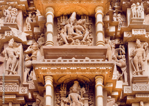 Indian architecture with figures of Lord Shiva and wife Parvati. Reliefs of historical temple in Khajuraho. UNESCO Heritage site, India