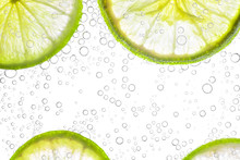 Close Up Fresh Lime Sliced In Soda Or Water Bubbles, Isolated On White Background