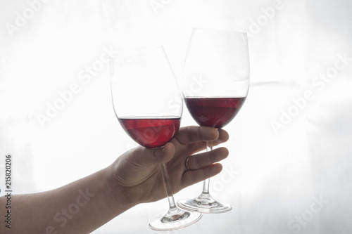In de dag Bar hand holding two wineglasses with red wine