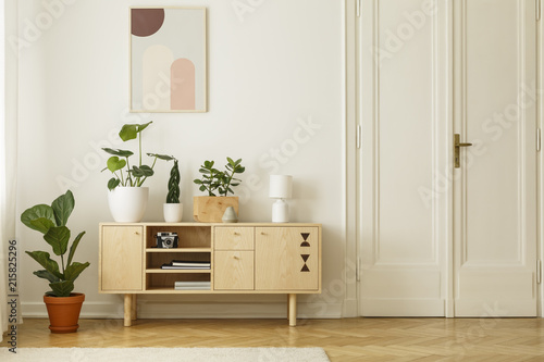 Retro style, wooden sideboard with green plants and a poster on a white wall in a simple apartment interior with herringbone hardwood floor Fototapet