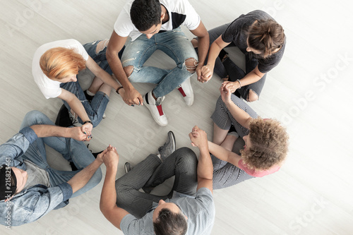 Top view on teenagers sitting in a circle and holding hands during group therapy Canvas Print
