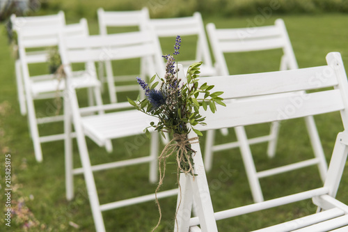 Fotografía  White wedding chairs decorated with fresh flowers on a green grass