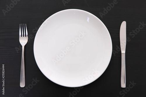 黒い木製テーブルに置かれた白い皿とカトラリー Wallpaper Mural