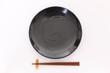 白いテーブルに置かれた黒い皿と箸