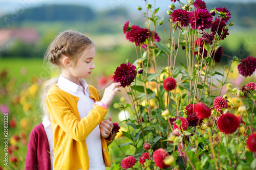 Photographie Cute little girl playing in blossoming dahlia field