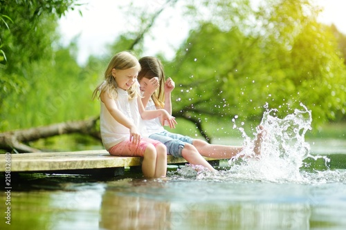 Obraz Two cute little girls sitting on a wooden platform by the river or lake dipping their feet in the water on warm summer day - fototapety do salonu
