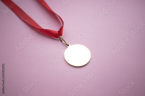 Photo  gold medal on a red ribbon on a pink background