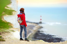 Young Female Tourist Enjoying Beautiful View Of White Chalk Cliffs Of The Seven Sisters At Birling Gap Coastline, Eastbourne, UK